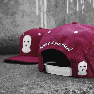 Mask Snapback in front of a wall