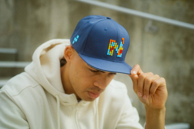 Man wearing a blue Nebelkind Cap with a pixelated and colorful N